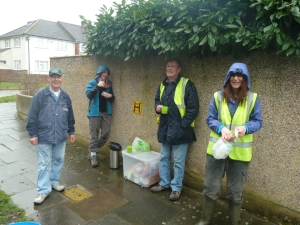 FotS volunteers seek temporary shelter from the rain under some overhanging shrubbery. Yikes! Cut it back at once!