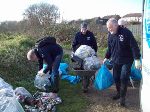 Regular Cray Riverkeeper volunteers Ray, Malcolm, Ron and Trevor shift the accumulated rubbish to the end of the footpath ready for collection by Bexley Council. Material in the clear bags  most of it discarded beer cans - has been separated for recycling. (Photo: Pamela Zollicoffer)